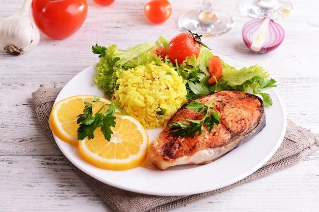 Saboroso peixe assado com arroz no prato e close-up da mesa