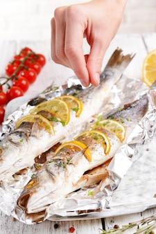 Saboroso peixe assado em papel alumínio na mesa