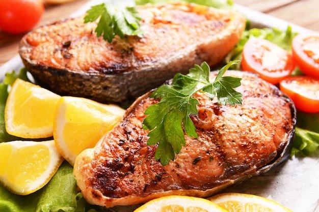 Saboroso peixe assado no prato e close-up da mesa