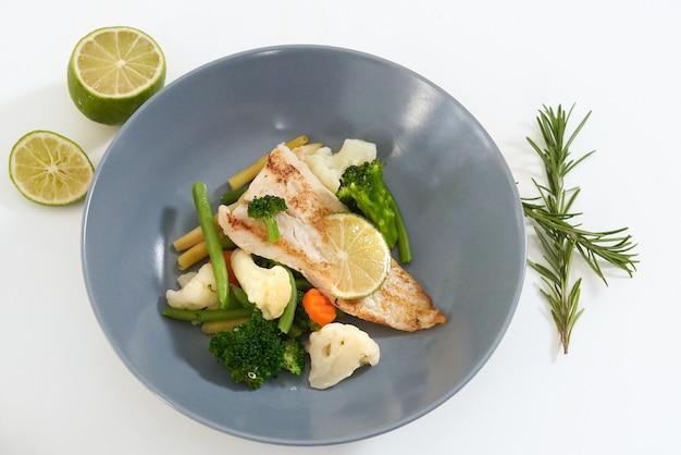 Saboroso peixe cozido no vapor e vegetais com raminho de alecrim