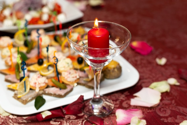 Saboroso prato com aperitivos e uma vela vermelha