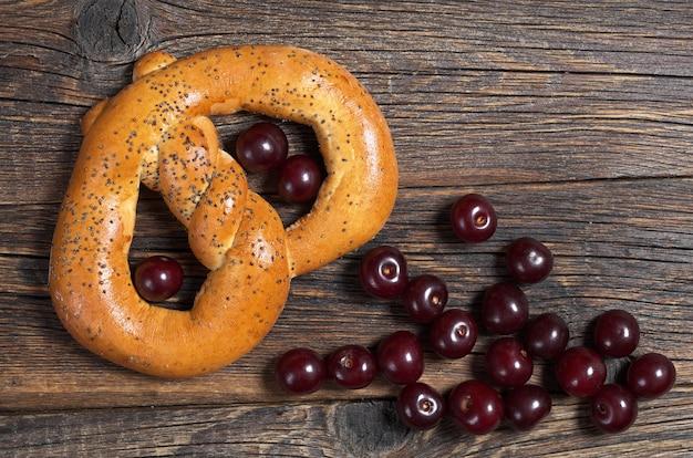 Saboroso pretzel com sementes de papoula e cereja no fundo de madeira, vista superior