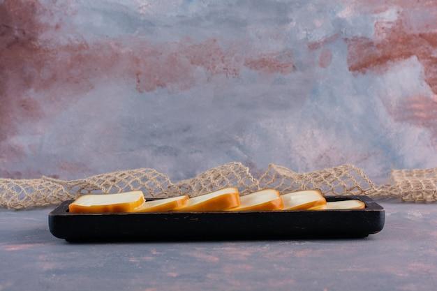 Saboroso queijo fatiado retangular em uma placa na superfície de mármore