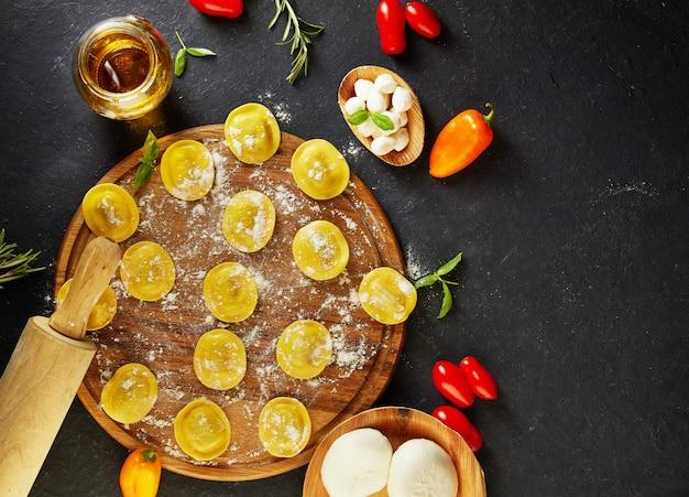 Saboroso ravióli cru com farinha, tomate cereja, óleo de girassol e manjericão na vista superior escura