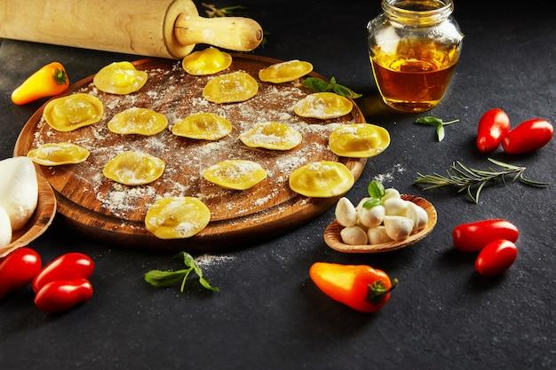 Saboroso ravióli cru com farinha, tomate cereja, óleo de girassol e manjericão no escuro