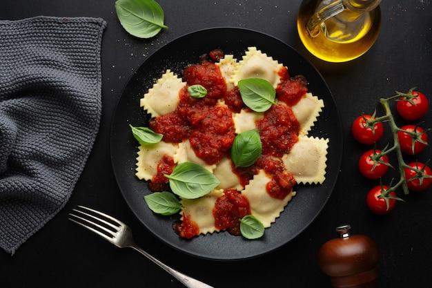 Saboroso ravióli italiano cozido com molho de tomate e manjericão servido no prato escuro.