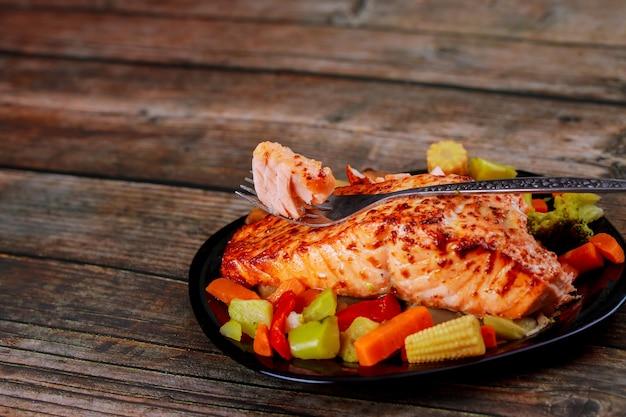 Saboroso salmão grelhado com legumes salteados asiáticos na placa preta com garfo. copie o espaço.