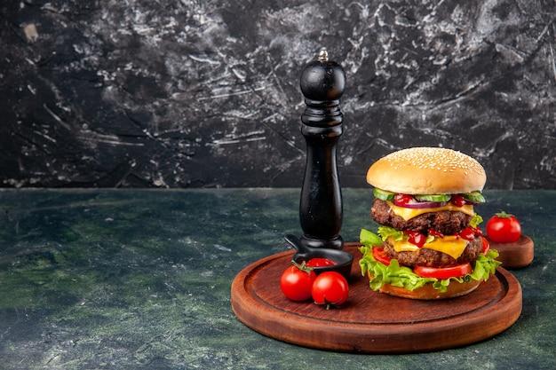 Saboroso sanduíche caseiro de tomate pimenta em uma tábua de corte em uma superfície de cor escura