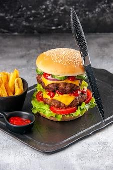 Saboroso sanduíche caseiro e garfo de ketchup com batatas fritas verdes no quadro negro sobre superfície cinza isolada