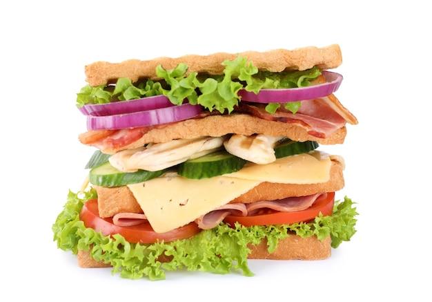 Saboroso sanduíche com frango, presunto e bacon isolado no branco