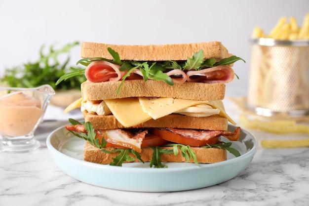 Saboroso sanduíche com frango, presunto e bacon servido em mesa de mármore branco