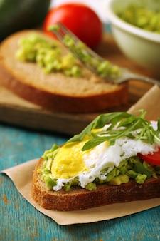 Saboroso sanduíche com ovo, abacate e vegetais em guardanapo de papel, mesa de madeira colorida