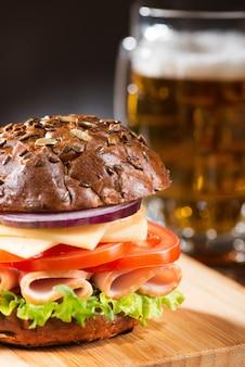 Saboroso sanduíche com salada verde, carne, queijo e tomate com uma caneca de cerveja