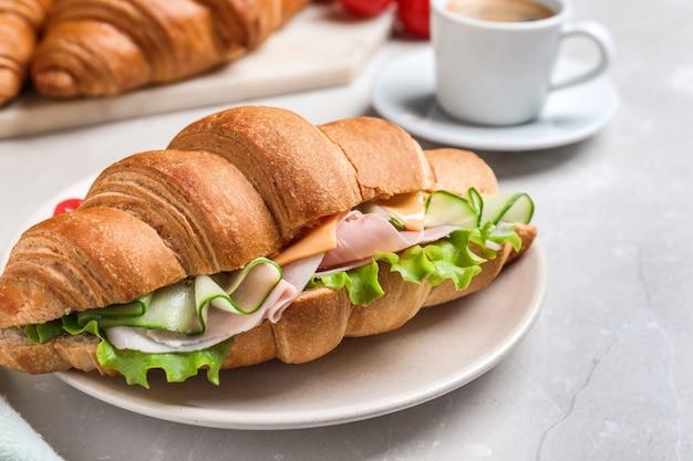 Saboroso sanduíche de croissant com presunto e pepino na mesa de luz, closeup