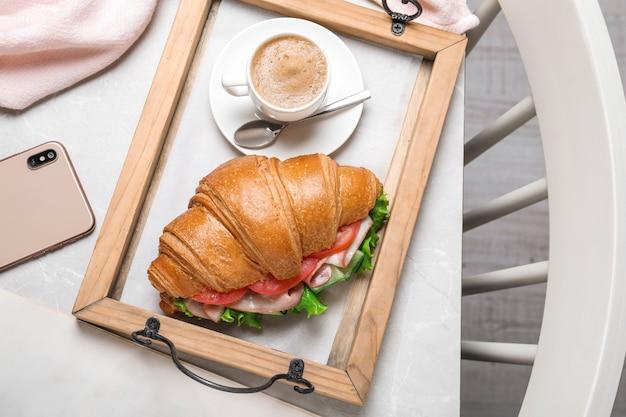 Saboroso sanduíche de croissant e café na mesa de mármore cinza claro, plano plano