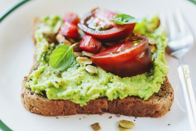 Saboroso sanduíche de pão integral com purê de abacate e tomate