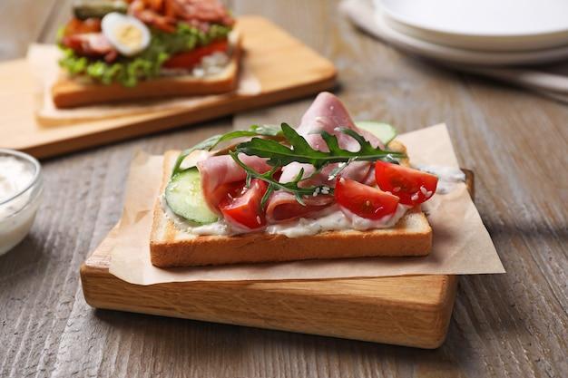 Saboroso sanduíche de presunto servido em mesa de madeira