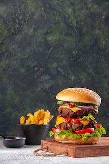 Saboroso sanduíche na tábua de madeira com batatas fritas na superfície desfocada