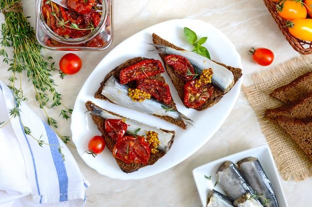 Saboroso smorrebrod em um prato branco sanduíches com pão de centeio preto, tomates secos ao sol anchovas salgadas mostarda