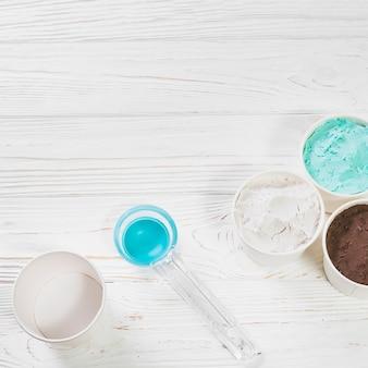 Saboroso sorvete napolitano perto de colher de plástico