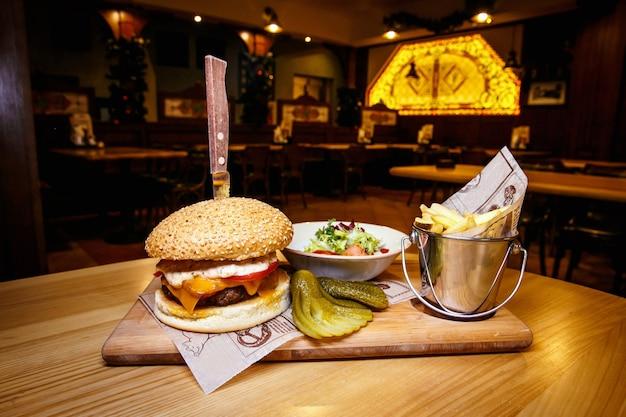 Saboroso steak burger com fatias de presunto em uma barra de madeira com batatas fritas, legumes e molho de mergulho.