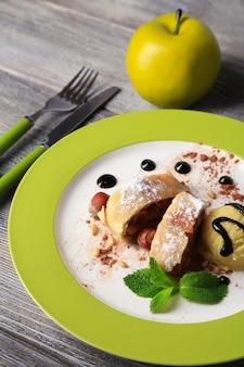 Saboroso strudel de maçã caseiro com nozes, folhas de hortelã e sorvete no prato, sobre fundo de madeira