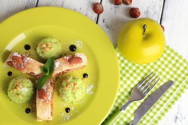 Saboroso strudel de maçã caseiro com nozes, folhas de hortelã e sorvete no prato
