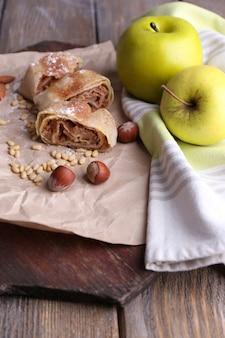 Saboroso strudel de maçã caseiro em guardanapo de papel, com fundo de madeira