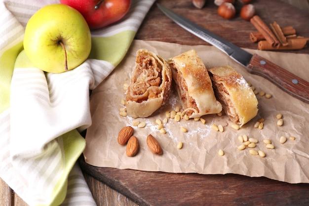 Saboroso strudel de maçã caseiro em guardanapo de papel, em superfície de madeira