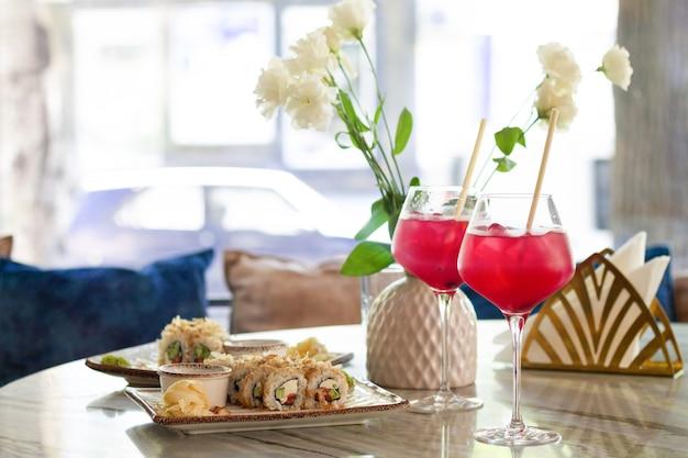 Saboroso sushi japonês fresco e bebidas na mesa em restaurante asiático luxuoso