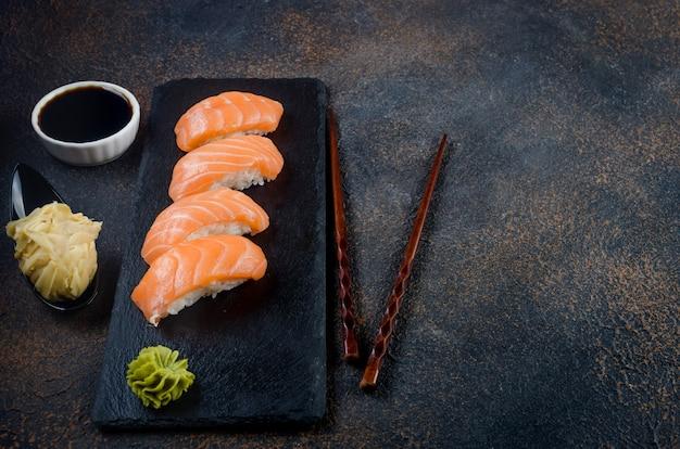Saboroso sushi nigiri com salmão em prato de pedra preta com molho de soja, gengibre, wasabi e pauzinhos