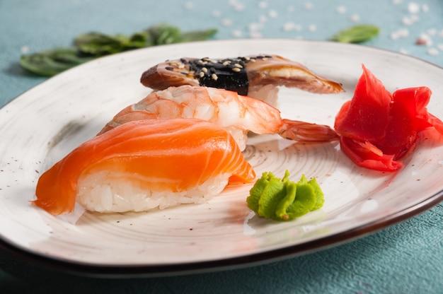 Saboroso sushi variado em um prato: salmão, camarão e enguia. moldura horizontal