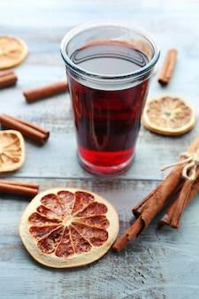 Saboroso vinho quente com especiarias e especiarias, em fundo azul de madeira, close-up