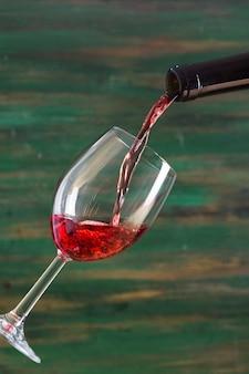 Saboroso vinho tinto, derramando em vidro