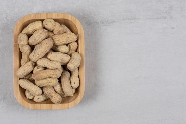 Saborosos amendoins crus na placa de madeira.