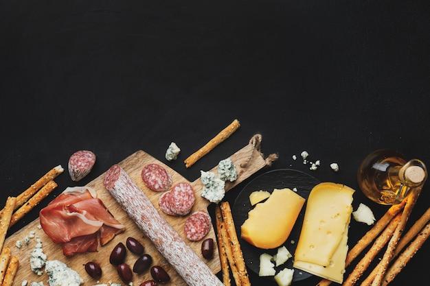 Saborosos aperitivos italianos clássicos em fundo escuro. vista de cima.