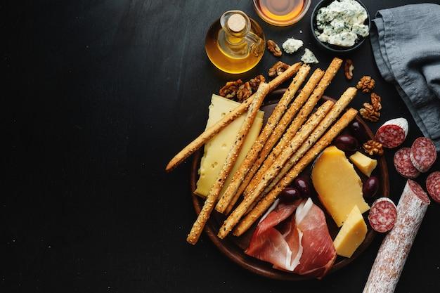 Saborosos aperitivos italianos clássicos na mesa escura. vista de cima.
