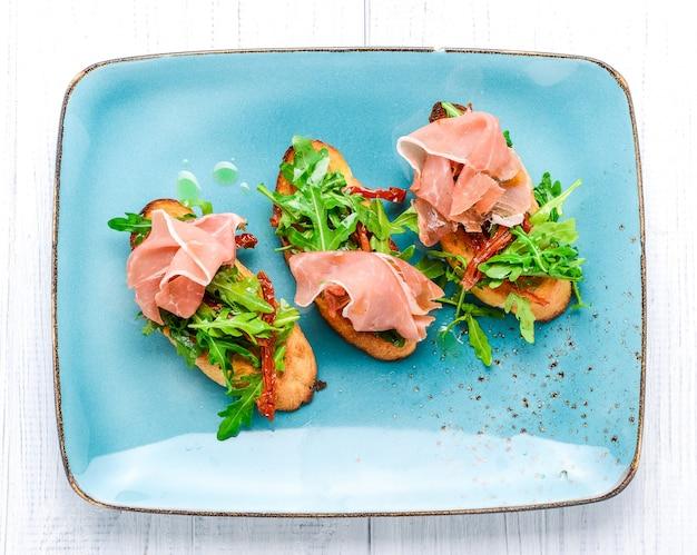 Saborosos aperitivos italianos salgados, ou bruschetta, em fatias de baguete tostada, guarnecidas com manjericão