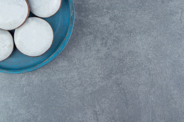 Saborosos biscoitos com cobertura no prato azul.