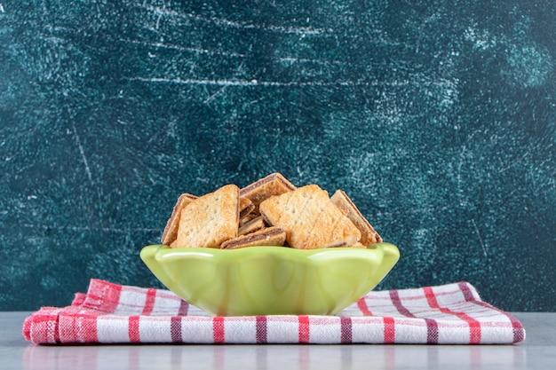 Saborosos biscoitos com recheio de chocolate em uma tigela verde.
