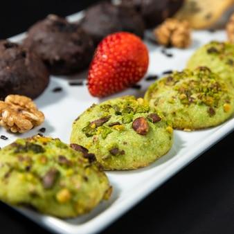 Saborosos biscoitos de chocolate coloridos no fundo preto