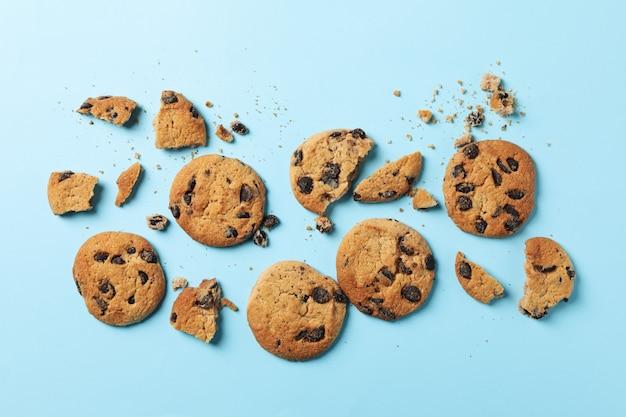 Saborosos biscoitos de chocolate em fundo azul, vista superior