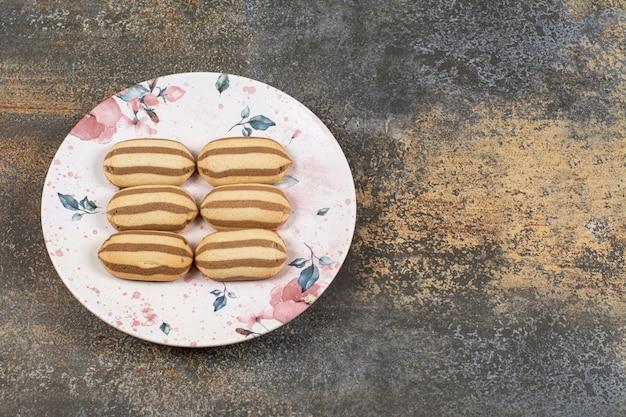 Saborosos biscoitos de chocolate listrados no prato colorido.
