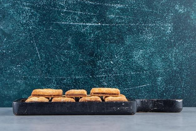 Saborosos biscoitos de cracker com recheio de chocolate na tábua de cortar preta.