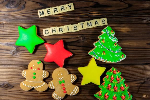 Saborosos biscoitos de gengibre de natal festivos e inscrição de feliz natal na mesa de madeira. vista do topo