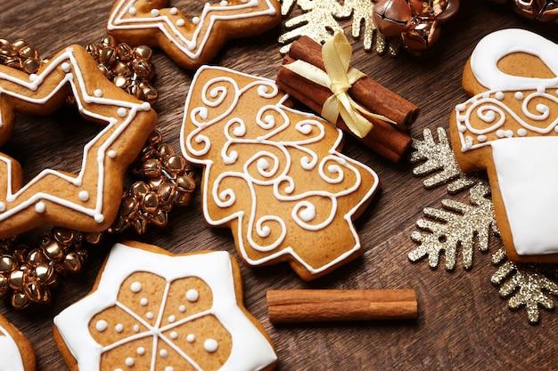 Saborosos biscoitos de gengibre e decoração de natal em fundo de madeira, close-up