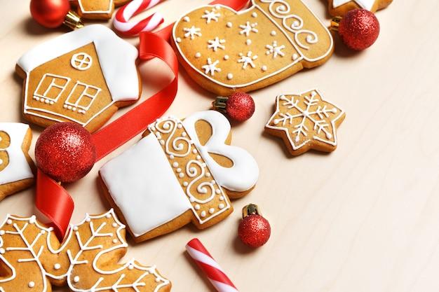 Saborosos biscoitos de gengibre e decoração de natal em fundo de madeira