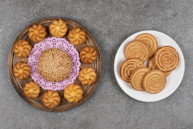 Saborosos biscoitos doces e biscoitos na placa de madeira.