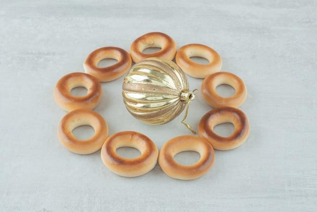 Saborosos biscoitos doces redondos com bola de natal dourada em fundo branco. foto de alta qualidade