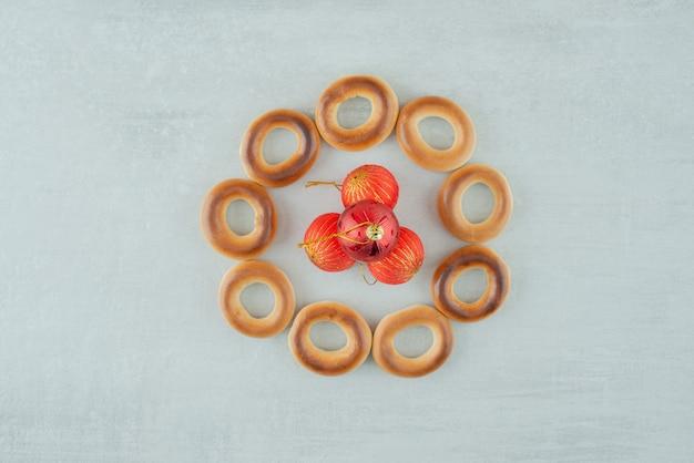 Saborosos biscoitos doces redondos com bolas de natal vermelhas em fundo branco. foto de alta qualidade